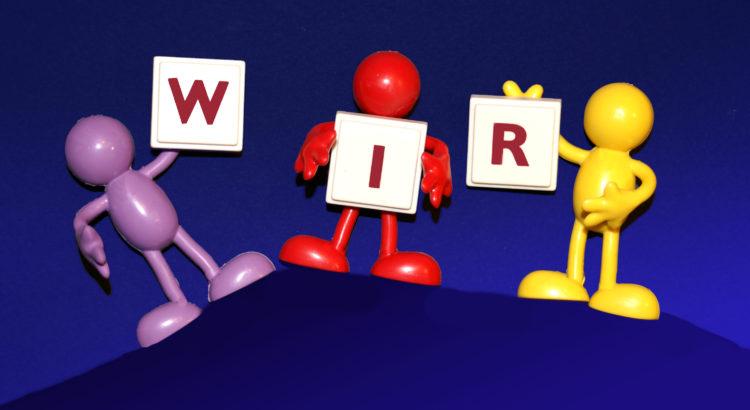 """Drei Puppen, die Buchstaben """"W.I.R"""" hochhalten"""