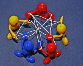 Puppen bilden mit Band ein Netzwerk ab