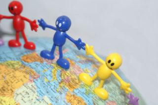 Püppchen bilden eine Menschenkette auf dem Globus